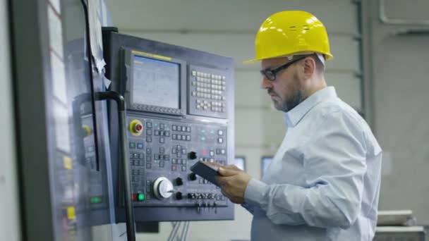 Inženýr je programování cnc frézka s tabletový počítač v továrně