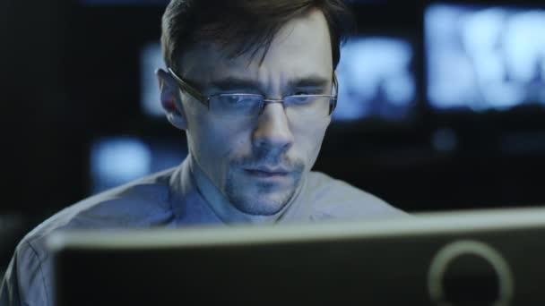 Koncentrované muž profesionální v brýlích pracuje na počítači v tmavé kanceláři místnosti