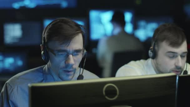 Tým z toho odborníků pracuje na počítači v tmavé kanceláři místnosti plné obrazovky