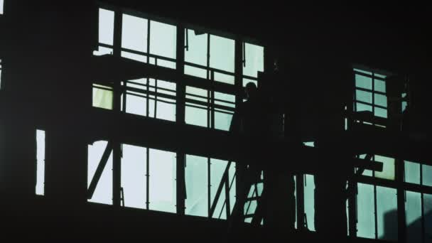Silhouette of Two Workers on Construction Site.
