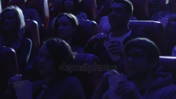 Emberek csoportja is nevetve, miközben néz mozi mozi-ban egy vígjáték filmvetítés.