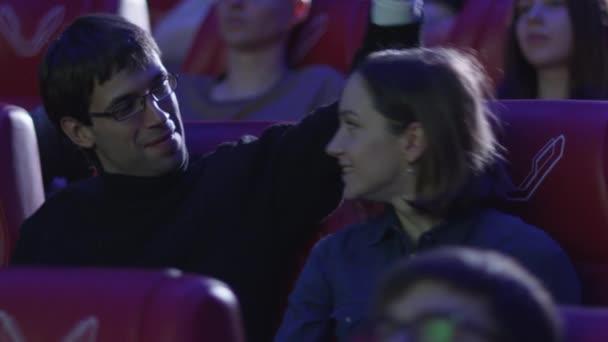 Fiatal, boldog, romantikus pár figyel egy film vetítés a mozi mozi.