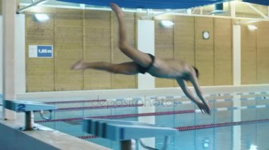 Professional Male Swimmer Jumping Off the Starting Block and Performing the Butterfly Stroke. Camera Follow Him.