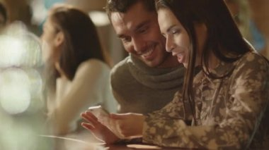 Man and woman laugh while using a smartphone and having a good time in a bar.