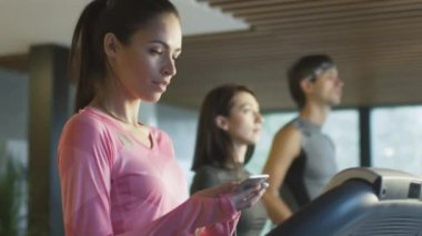 Fit athletic caucasian girl is running on treadmill in sport gym with earphones and phone.