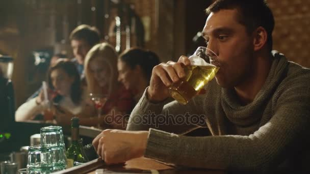 Attractive man is drinking lager beer in a crowded pub.