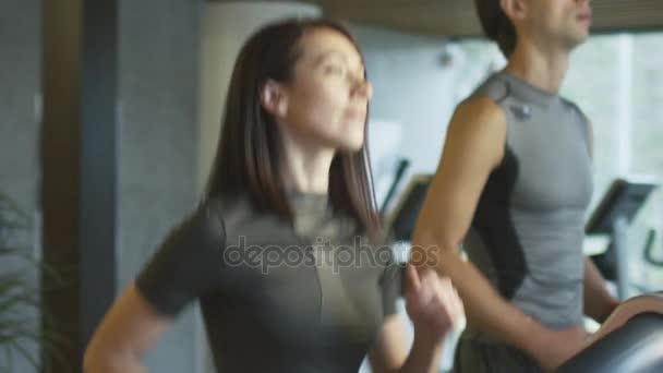 Slow-Motion Aufnahmen von jungen sportlichen Männern und Frauen trainieren und laufen auf dem Laufband im Fitnessstudio sport.