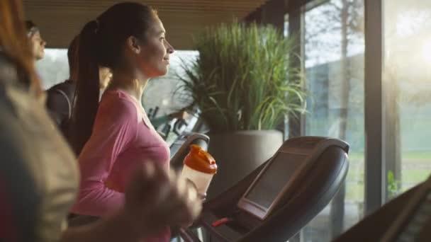fittes athletisches Mädchen trinkt Proteinshake während des Trainings auf dem Laufband in der Sporthalle.