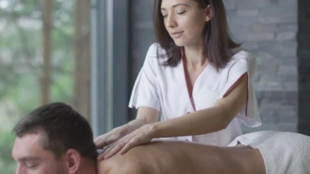 Pohledný muž, dostává od maséra žena relaxační masáž ve wellness centru.