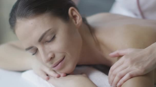 Krásná žena, dostává z ženské masér relaxační masáž ve wellness centru.