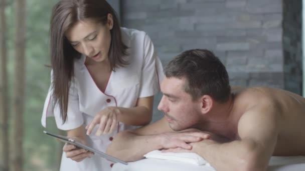 Frau Masseur zeigt eine Tablette Mann während einer entspannenden Behandlung im Wellness-center