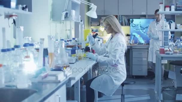 Wissenschaftlerin arbeitet im Labor mit Kollegen an einer Mikropipette.
