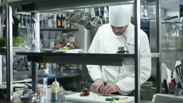 Profesionální kuchař v komerční kuchyni je krájení zeleniny.