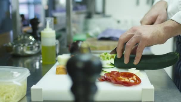 Professional chef in a commercial kitchen in a restaurant or hotel is slicing green vegetables.