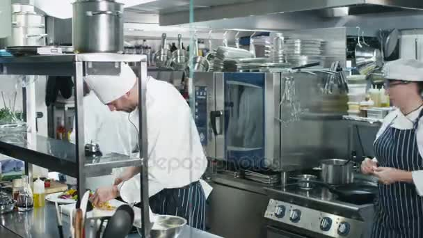 Časosběrné záběry tří profesionálních kuchařů v komerční kuchyni v restauraci či hotel, příprava jídla.