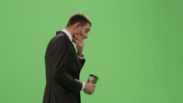 Unavený podnikatel v obleku chodí s kávou na imitaci fabion v pozadí.