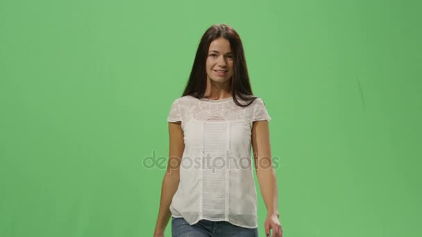 Casual brunette female is walking on a mock-up green screen in the background.