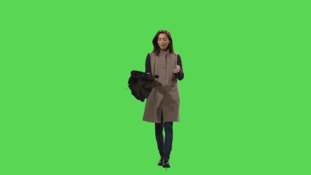lässige brünette Frau bemerkt den Regen beim Gehen und öffnet einen Regenschirm auf einer grünen Leinwand im Hintergrund.