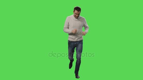 Lässiger Mann im Mantel läuft auf einer grünen Leinwand im Hintergrund.