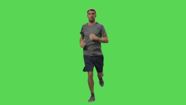 Man in a t-shirt and shorts is jogging on a mock-up green screen in the background.