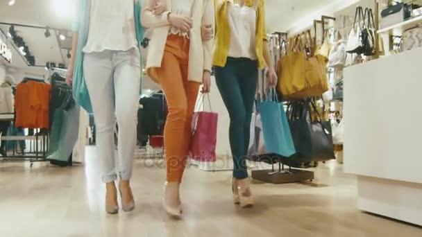 Výstřel z ženských nohou, chůzi směrem k fotoaparátu prostřednictvím obchodu v barevné oděvy, tašky