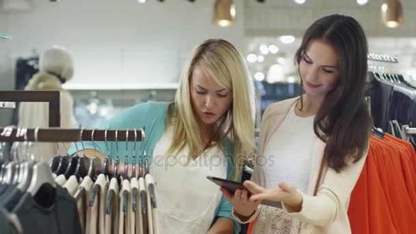 82a75da2271 Two happy young girls are shopping clothes and checking a tablet computer  in a department store.– stock footage