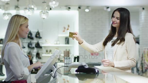 Fiatal barna lány biztosít hitelkártya hoz pénztáros-on egy áruházban pénztári