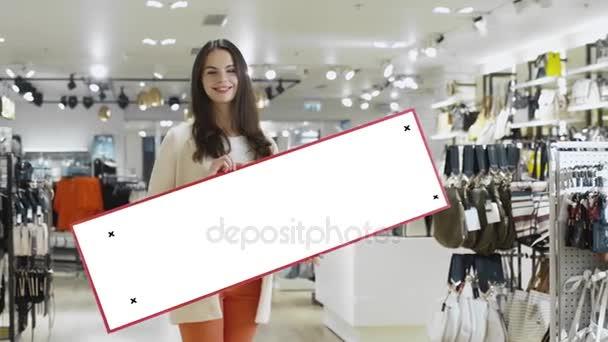 Mladá usměvavá brunetka žena drží znak prázdné maketa v obchodním domě.