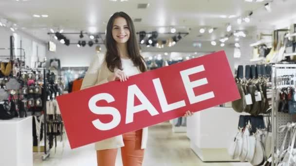 Mladá usměvavá brunetka je přehodit znaménko prodej v obchodním domě