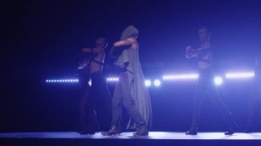 African american male in a hoodie leads a group of dancers while singing on a dark stage with lights.