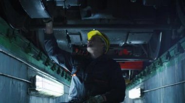 Technician in Hard Hat with Hammer in Hand Inspecting Train