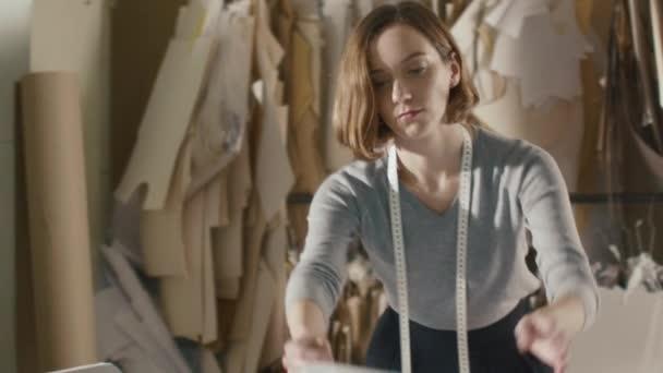 Designer-Kleidung arbeitet mit Schnittmuster auf einem Studio-Tisch ...