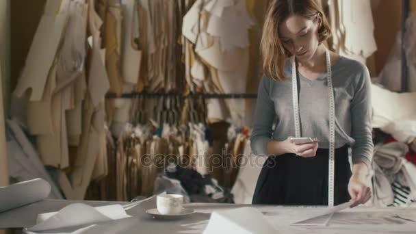 Weibliche Kleidung Designer ist Schnittmuster mit einem Smartphone ...
