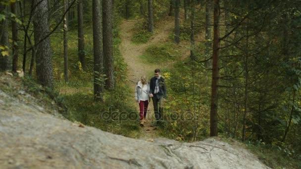 Pár je pěší a jít do kopce v podzimní lesní stezka