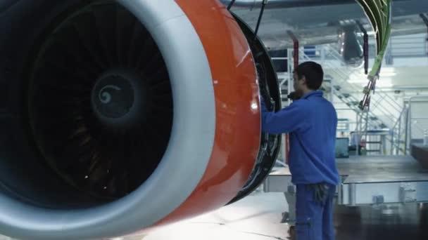 Mechanik údržby letadel s problikávajícím světlem kontroluje motor letadla v hangáru.