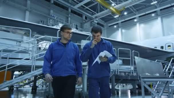 Dvě letadla údržby mechaniky mají konverzaci při kontrole doklady v hangáru letadlo s letadlem v pozadí