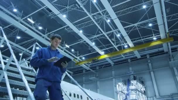 Mechanik údržby letadel v modré uniformě jde dolů po schodech při používání tabletu v hangáru.