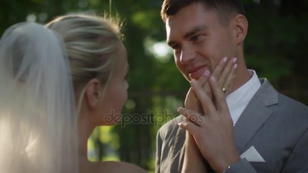 Šťastná nevěsta a ženich držet za ruce v sunny park