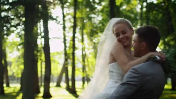Sposa e lo sposo si abbracciano in un parco pieno di sole