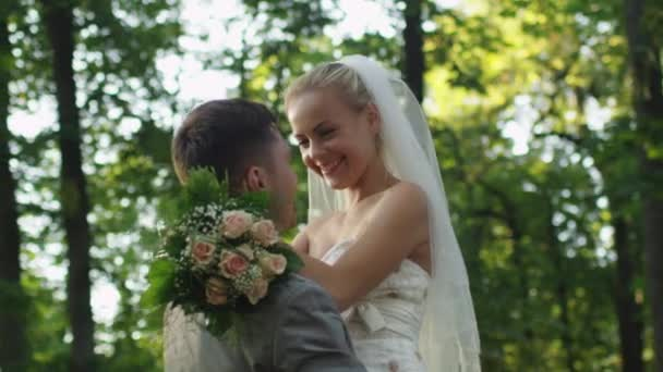 Nur verheiratete Paare umarmen einander in einem sonnigen park.