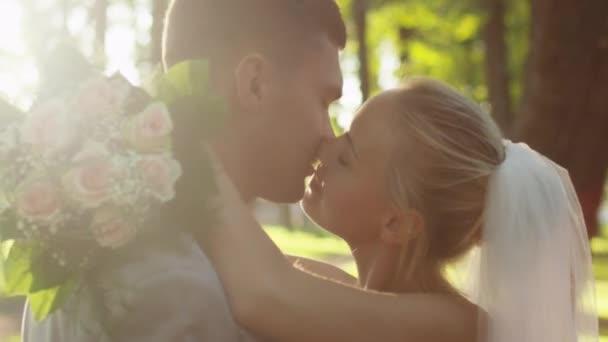 Mladá nevěsta a ženich jsou líbání v sunny park