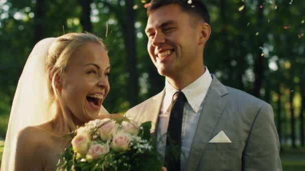glückliche Braut und Bräutigam lachen und werden im sonnigen Park von Konfetti überrascht.