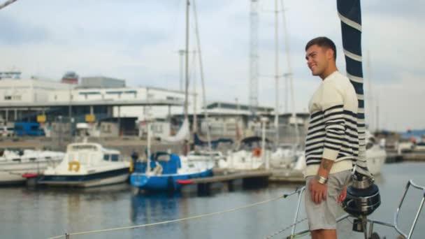 Fiatal férfi lebegő port és más jachtok elhaladó vitorlás.