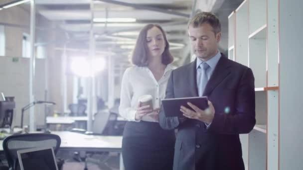 zwei Büroangestellte zu Fuß. Geschäftsmann hält Tablet in den Händen.