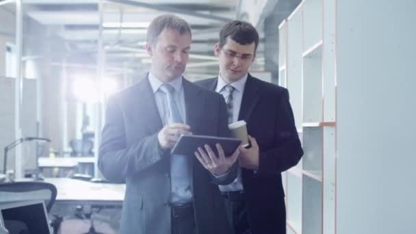 Dva podnikatelé jsou Walking prostřednictvím úřadu. Office pracovník podniku Tablet Pc.