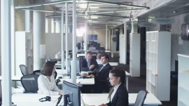 Administrativní pracovníci pracují na počítačích.