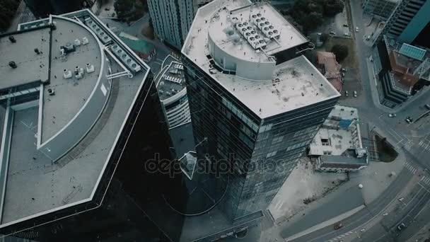 Aerial drone shot of a city downtown with glass skyscrapers and traffic.