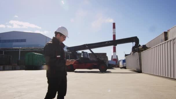Arbeiter benutzt Tablet im Logistikzentrum. Containerhandler im Hintergrund.