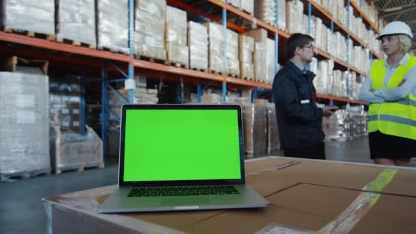 Laptop with Green Screen in Logistics Warehouse. Great for Mock-up usage.