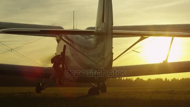 Parašutista se v vrtule letadla ve světle západu slunce